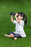 Asian Chinese little girl looking through binoculars. Asian Chinese little girl sitting on the grass and looking through binoculars at outdoor park stock photos