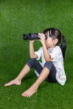 Asian Chinese little girl looking through binoculars. Asian Chinese little girl sitting on the grass and looking through binoculars at outdoor park royalty free stock image