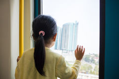 Asian Chinese little girl looking far way beside the window. Asian Chinese little girl inside a MRT transit looking far way beside the window Royalty Free Stock Images
