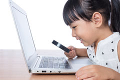 Asian Chinese little girl looking at laptop through magnifier. In isolated white background Stock Images