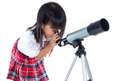 Asian Chinese little girl looking through telescope Stock Photo