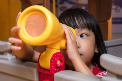Asian Chinese little girl looking through a toy telescope Royalty Free Stock Photos