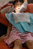 Asian Chinese little girl lying down for tooth extraction Royalty Free Stock Image