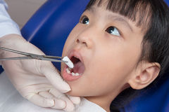 Asian Chinese little girl lying down for tooth extraction. At dental clinic Royalty Free Stock Photography