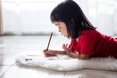 Asian Chinese little girl lying on the floor drawing in the livi Royalty Free Stock Photos