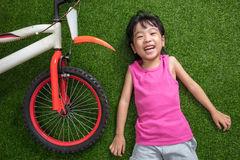 Asian Chinese little girl lying on the grass with bicycle Royalty Free Stock Photos