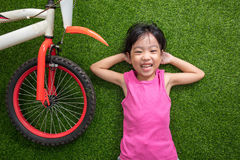 Asian Chinese little girl lying on the grass with bicycle Stock Photo