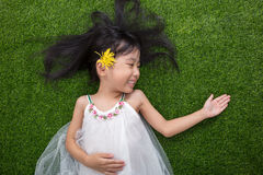 Asian Chinese little girl lying on the grass with flower Stock Photo