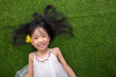 Asian Chinese little girl lying on the grass with flower Stock Image