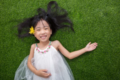 Asian Chinese little girl lying on the grass with flower Stock Images