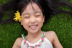 Asian Chinese little girl lying on the grass with flower Stock Photos