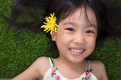 Asian Chinese little girl lying on the grass with flower Royalty Free Stock Photography