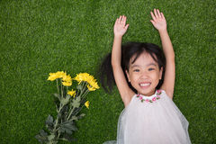 Asian Chinese little girl lying on the grass with flowers Royalty Free Stock Photo