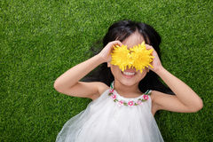 Asian Chinese little girl lying on the grass with flowers Royalty Free Stock Photography