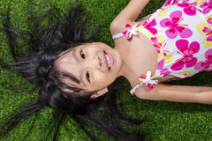 Asian Chinese little girl lying on the grass Stock Photo