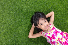 Asian Chinese little girl lying on the grass Royalty Free Stock Images