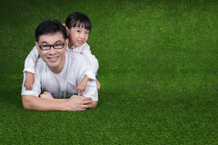 Asian Chinese little girl lying on her father`s back Royalty Free Stock Photo