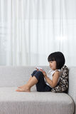 Asian Chinese little girl lying on the sofa with phone Stock Images