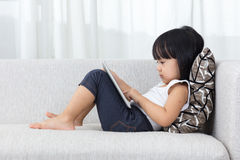 Asian Chinese little girl lying on the sofa with tablet Royalty Free Stock Image