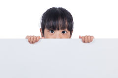 Asian Chinese little girl peeping behind white board. In isolated white background stock image