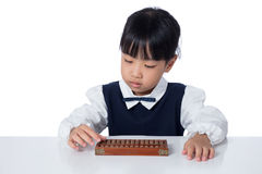 Asian Chinese little girl playing abacus. In isolated white background Stock Image