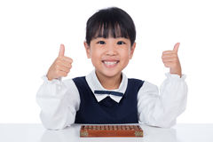 Asian Chinese little girl playing abacus. In isolated white background Stock Photo