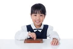 Asian Chinese little girl playing abacus. In isolated white background Royalty Free Stock Image