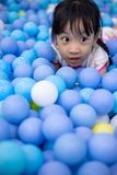 Asian Chinese little girl playing at balls pool royalty free stock photo