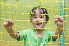 Asian Chinese little girl playing behind the net Stock Images