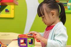 Asian Chinese little girl playing colorful magnet plastic blocks. Kit at indoor playground Stock Images
