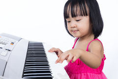 Asian Chinese little girl playing electric piano keyboard. In the living room at home Stock Photo
