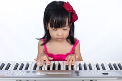 Asian Chinese little girl playing electric piano keyboard. In the living room at home Royalty Free Stock Images