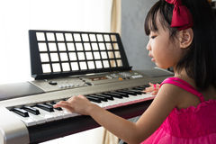 Asian Chinese little girl playing electric piano keyboard Royalty Free Stock Image