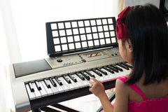 Asian Chinese little girl playing electric piano keyboard. In the living room at home Royalty Free Stock Photo