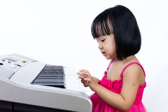 Asian Chinese little girl playing electric piano keyboard Royalty Free Stock Photo