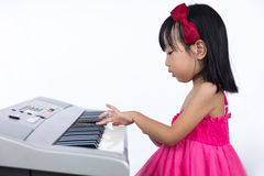 Asian Chinese little girl playing electric piano keyboard Stock Image