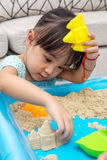 Asian Chinese little girl playing kinetic sand at home Royalty Free Stock Image