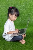 Asian Chinese little girl playing with laptop Royalty Free Stock Photos