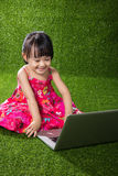 Asian Chinese little girl playing laptop Stock Images