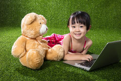 Asian Chinese little girl playing laptop with teddy bear Stock Images