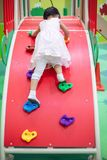 Asian Chinese little Girl playing at mini rock climbing wall royalty free stock photos