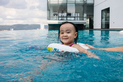 Asian Chinese little girl playing at the outdoor swimming pool Royalty Free Stock Photography