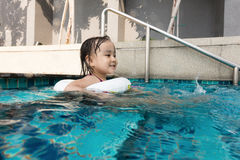 Asian Chinese little girl playing at the outdoor swimming pool Royalty Free Stock Image