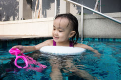Asian Chinese little girl playing at the outdoor swimming pool Stock Photo