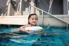 Asian Chinese little girl playing at the outdoor swimming pool Stock Image