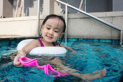 Asian Chinese little girl playing at the outdoor swimming pool Stock Photography