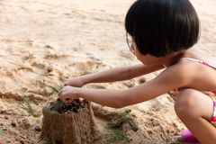 Asian Chinese little girl playing sand at beach stock photos