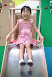 Asian Chinese little girl playing on the slide royalty free stock photography