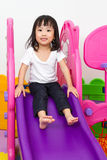 Asian Chinese little girl playing on the slide. At indoor colourful playground Stock Photography