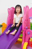 Asian Chinese little girl playing on the slide. At indoor colourful playground Royalty Free Stock Photos